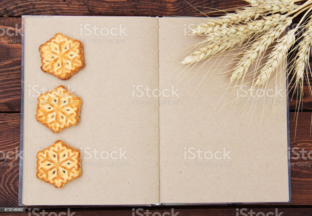 Open recipe book with blank pages, homemade Christmas cookies and cereals. Christmas concept. Holiday cookies in the shape of snowflakes. Copy space. stock photo