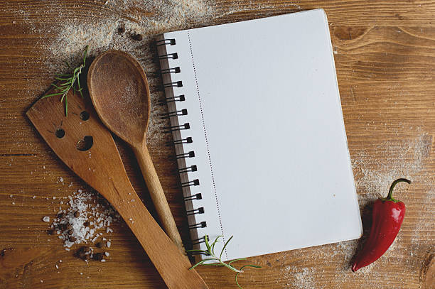 Open recipe book with wooden spoon, spatula and spices stock photo