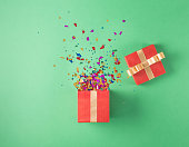 Open red gift box with various party confetti on a green background