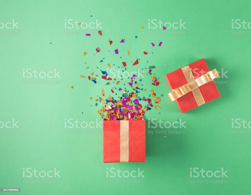 Open red gift box with various party confetti on a green background stock photo