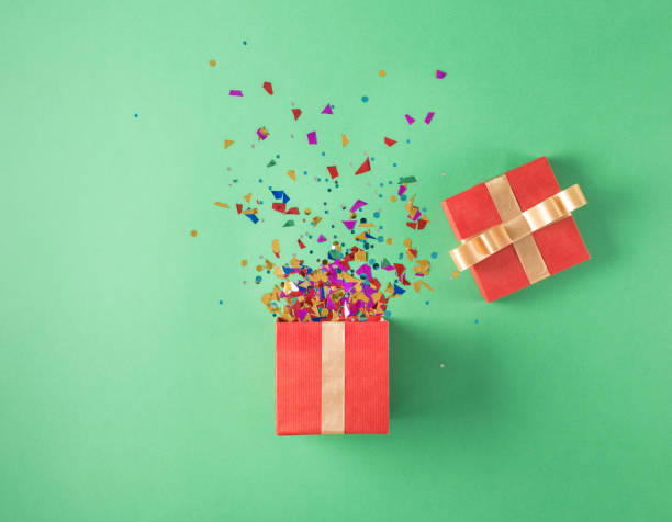 open red gift box with various party confetti on a green background - birthday gift stock photos and pictures