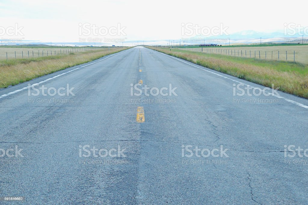 Open road through grasslands in Montana. stock photo