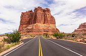 A road in Arches National Park, near Moab in Utah, leading towards a very large rock formation.