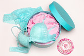 Open round gift box with blue lingerie set and pink flower, top view