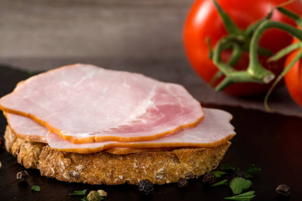 Open sandwich with pork smoked ham on a dark slate stock photo