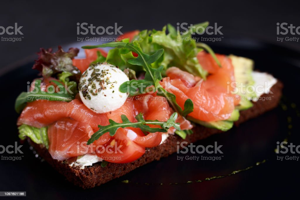 open sandwich with salmon, avocado and mozzarella stock photo