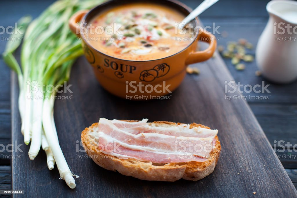 Open sandwich with smoked bacon and pumpkin cream soup royalty-free stock photo
