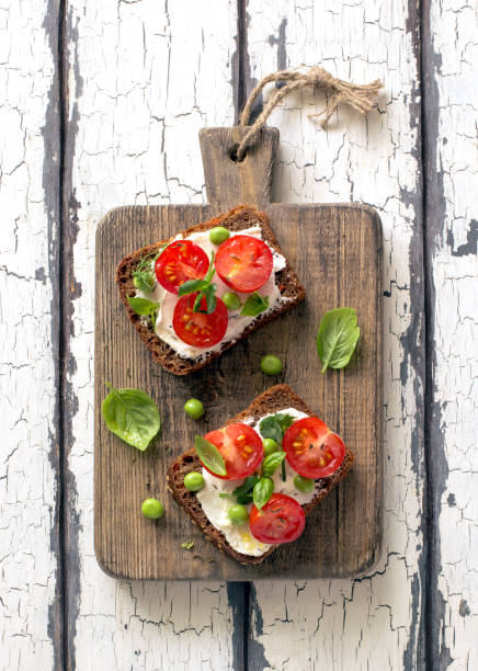 Open sandwiches with cream cheese, cherry tomatoes, green peas and basil close up stock photo