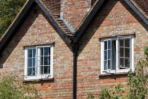 Open sash windows on a classic English country cottage house. Ventilation on a hot summers day for this beautiful old red brick building in the south of England.