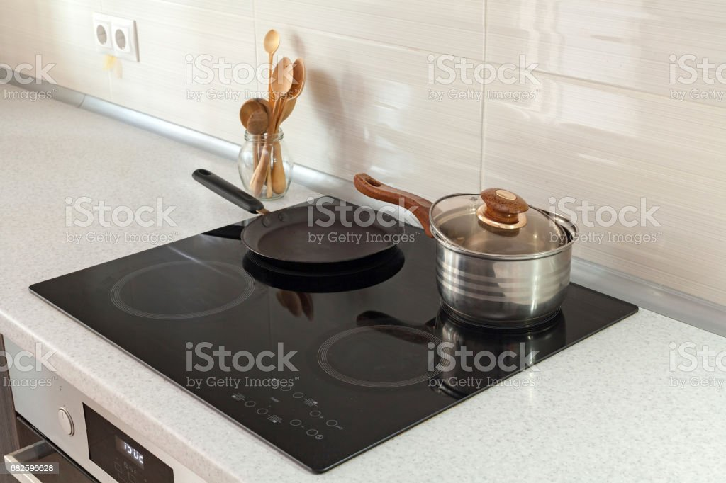 Open saucepan, pan and wooden spoons in modern kitchen with induction stove stock photo