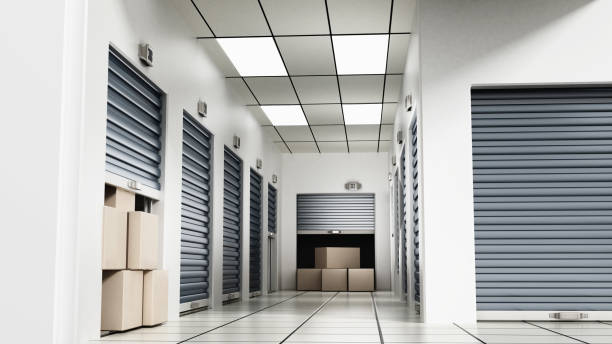 Open self storage units full of cardboard boxes among closed doors stock photo