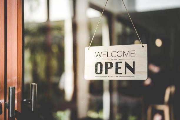 カラフルなボケライト抽象的な背景を持つカフェの前にぶら下がるオープンサイン。ビジネスサービスと食品のコンセプト。ヴィンテージトーンフィルター効果カラースタイル。 - 店 ストックフォトと画像