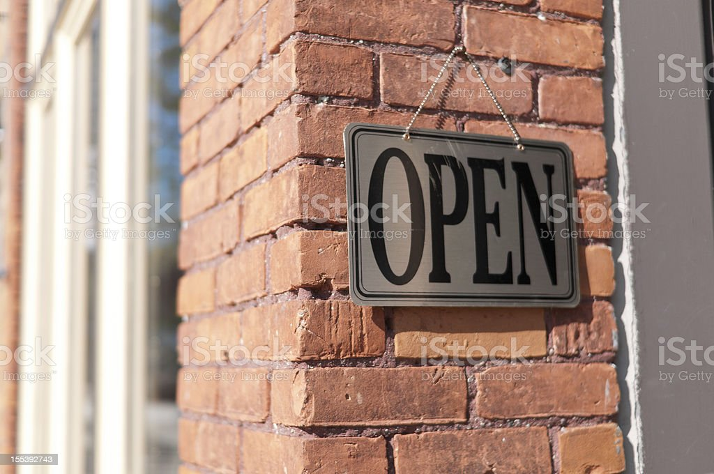 Open sign hanging on a brick wall royalty-free stock photo