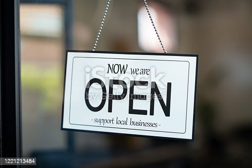 Reopening of a small business activity after the covid-19 emergency, ended the lockdown and quarantine. A business sign that says now we are open support local businesses on cafe or restaurant hang on door at entrance. Close up of open sign on the window of shop or store.