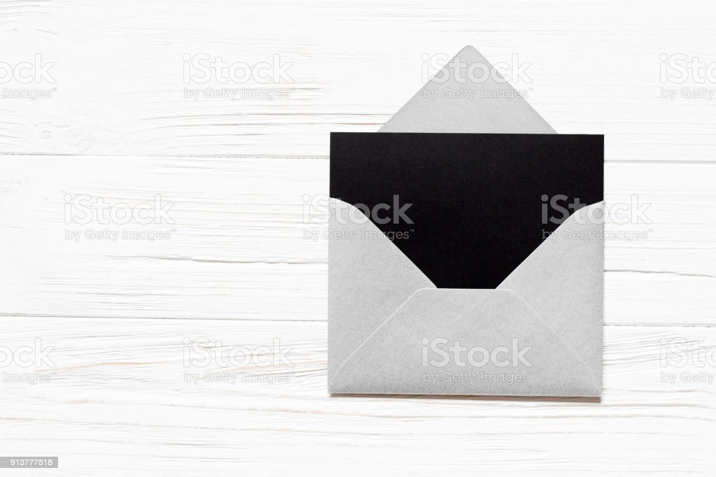 Open silver envelope and black paper blank on white wooden background. Mockup for greeting card. stock photo