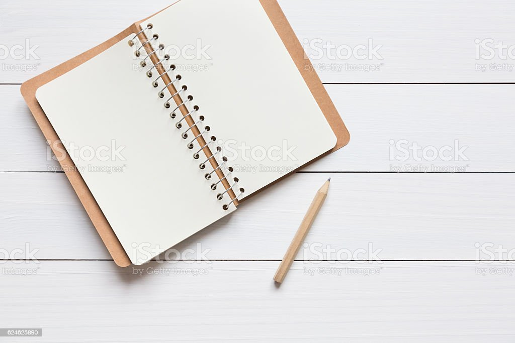 Open sketchbook and pencil on the white wooden table stock photo