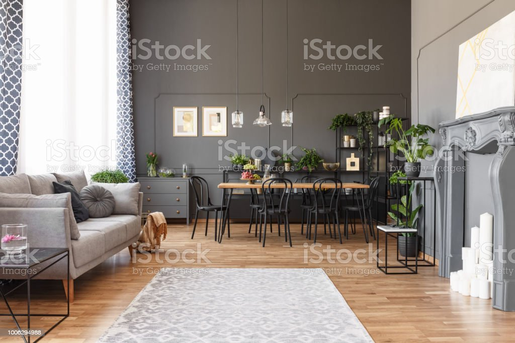 Open space apartment interior with gray sofa next to the window, dining table with black chairs and molding on the walls. Real photo stock photo