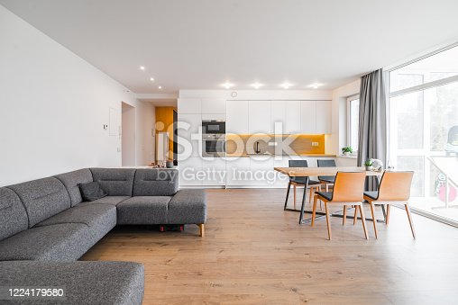 Modern and bright apartment interior with white colours, some wood details and bright colours. Dining room connected with kitchen and with living room.
