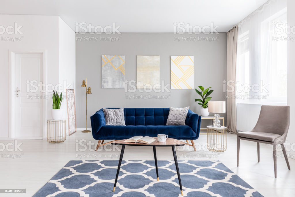 Picture of: Open Space Living Room Interior With Modern Furniture Of A Navy Blue Settee A Beige Armchair A Coffee Table And Other Objects In Gold Color Real Photo Stock Photo Download Image