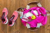 スポーツ バッグを開き、木の床の上面にピンクのランニング シューズ