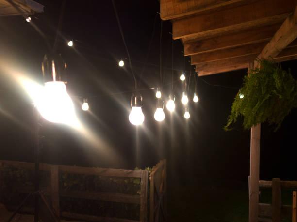 open string lights hanging in a row against garden - terrassen lichterketten stock-fotos und bilder