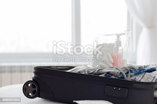 istock Open suitcase on a bed in the room 636350550
