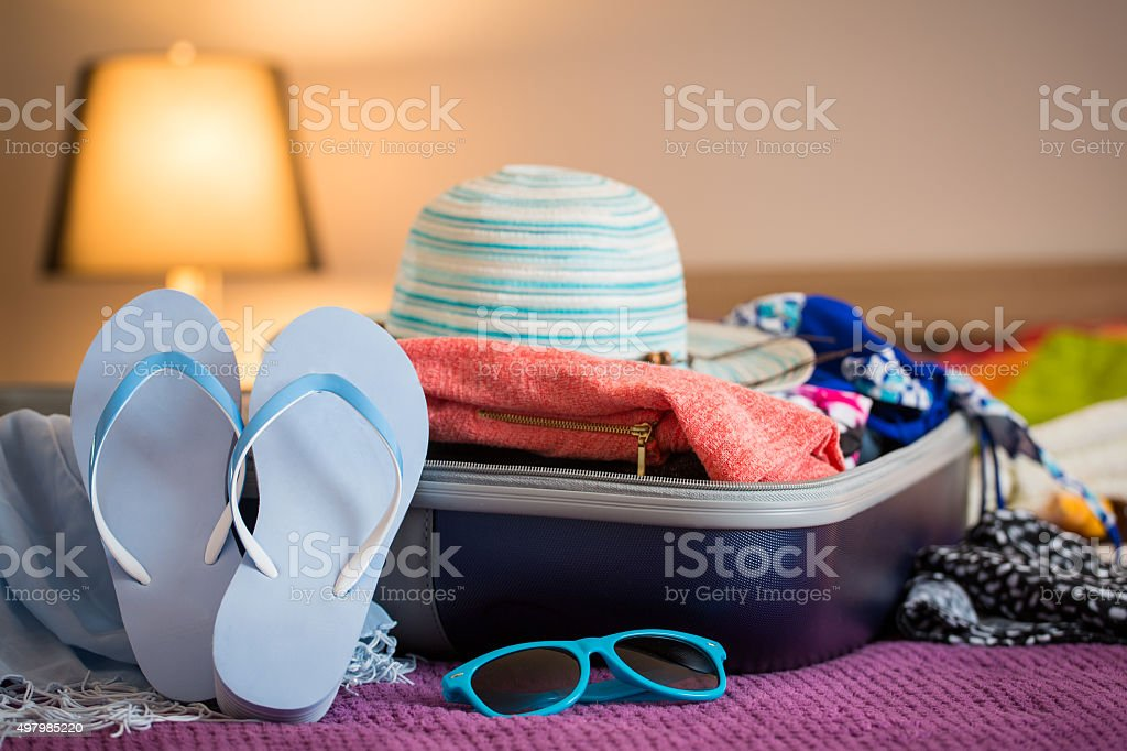 Open suitcase on bed stock photo