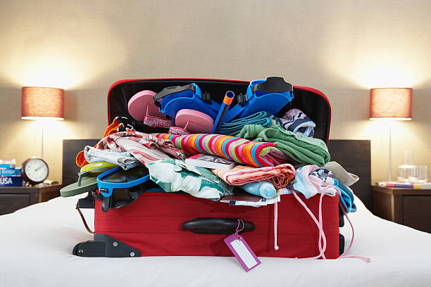 open suitcase on bed - overflowing stock photos and pictures