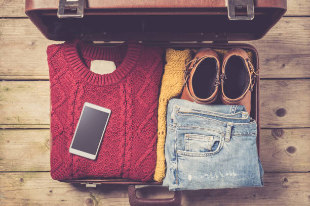 Open suitcase with casual female clothes stock photo