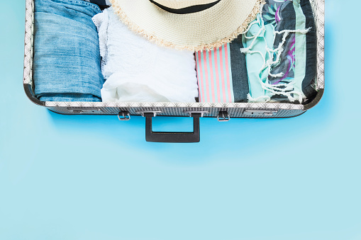 istock Open suitcase with female clothes for trip on pastel blue. Top view with copy space. Summer concept travel. 1018446390