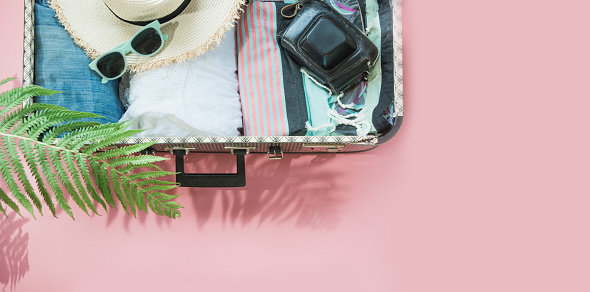 istock Open suitcase with female clothes for trip on pastel pink. Top view with copy space. Summer concept travel. 1018446404