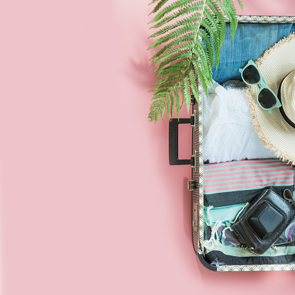 istock Open suitcase with female clothes for trip on pastel pink. Top view with copy space. Summer concept. 1147479842