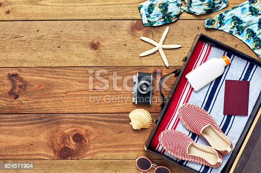 941183588 istock photo Open suitcase with summer vacation equipment flat lay on wood 624511904