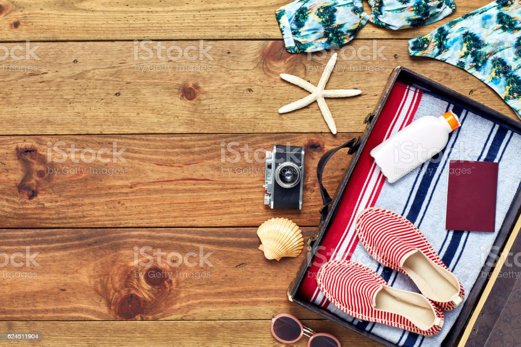 Open suitcase with summer vacation equipment flat lay on wood stock photo
