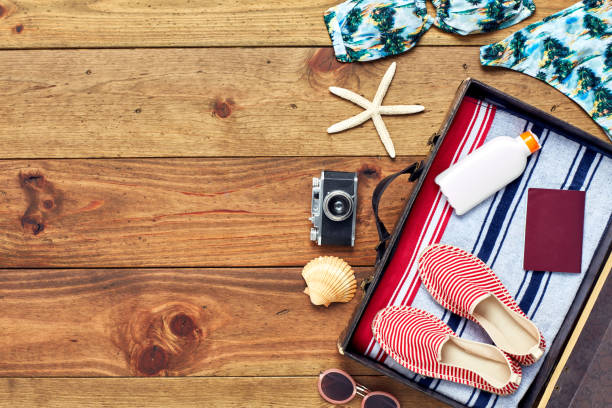 Open suitcase with summer vacation equipment flat lay on wood Directly above shot of open suitcase with summer vacation equipment .Flat lay of travel and beach accessories. The travel essentials are placed on right side of hardwood floor. knolling concept stock pictures, royalty-free photos & images