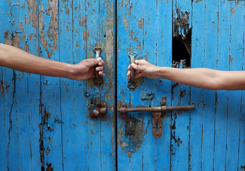 Two hands opening wooden door.