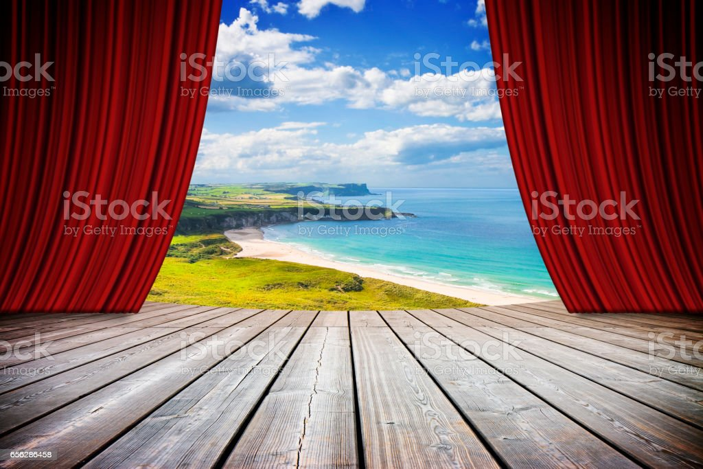 Open theater red curtains against Irish landscape - concept image stock photo