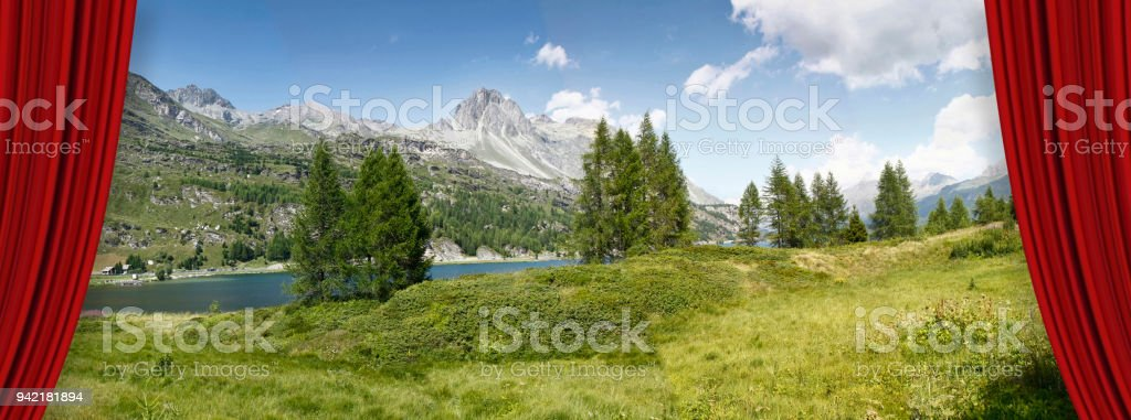 Open theater red curtains against Sils lake in the Upper Engadine Valley in a summer day (Europe -Switzerland) - concept image stock photo