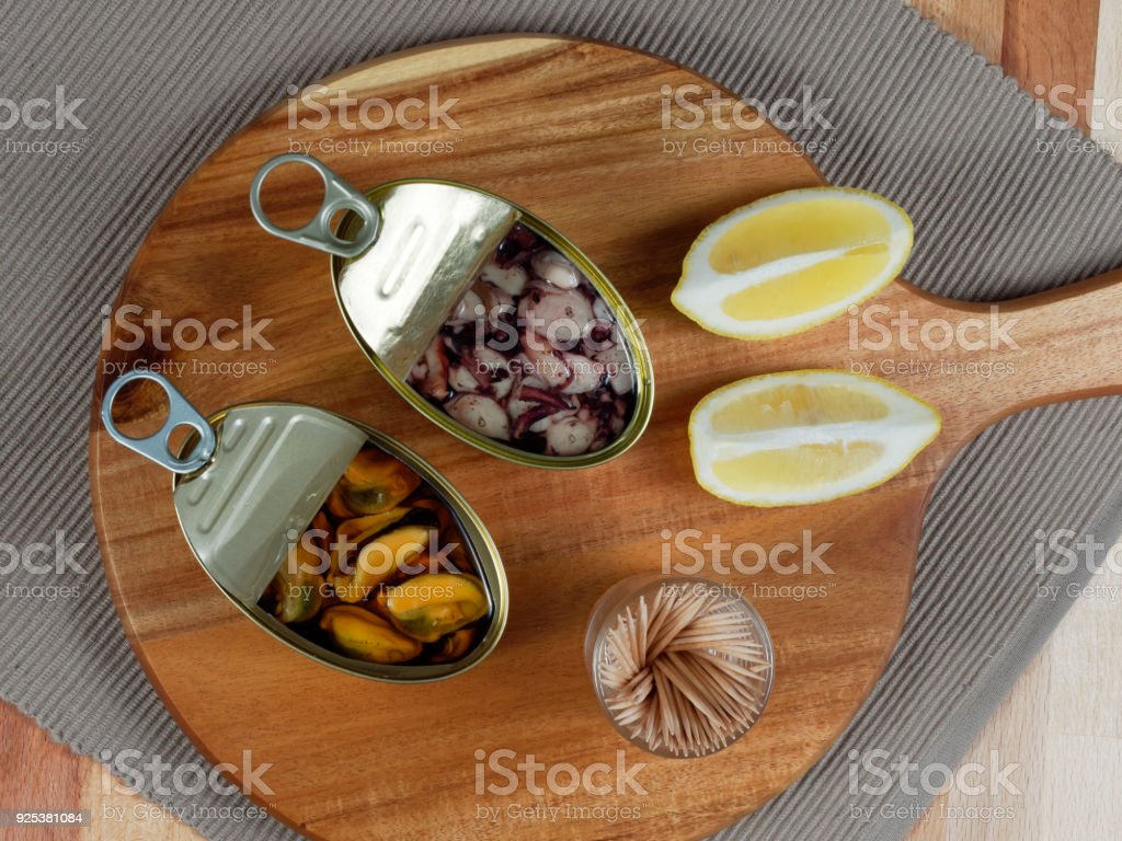 Open tin cans of mussels and octopus on a rustic wooden board stock photo