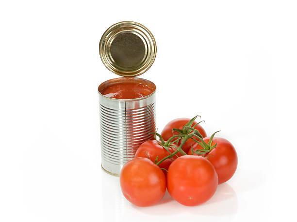 open tin of canned tomatoes next to a vine of fresh ones - tomato can stock photos and pictures