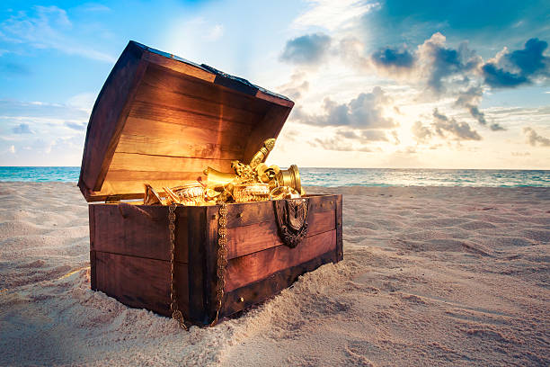 open treasure chest on the beach - pirates stock photos and pictures