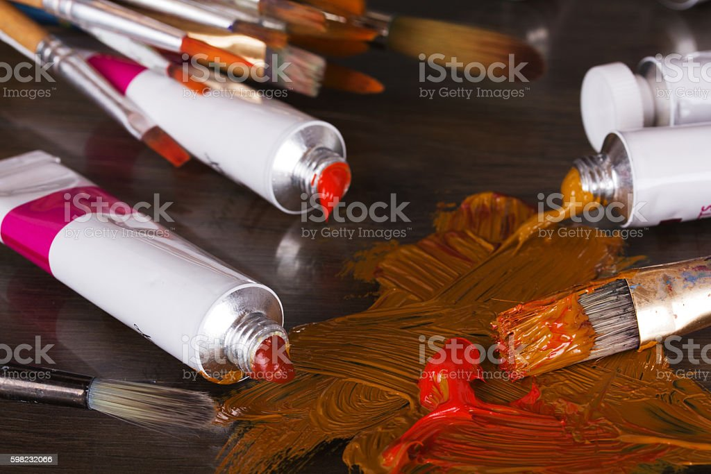 Open tubes of brown paint and brushes foto royalty-free