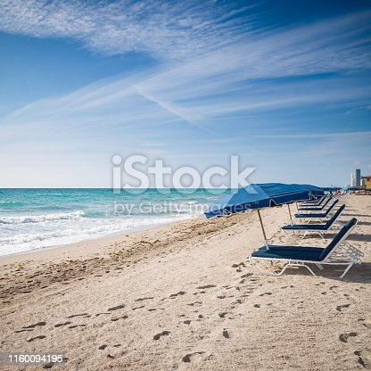 Open umbrellas on the sandy shore near the ocean. Beach in Miami, Florida. Empty beach. Seaside. Early morning. Clouds