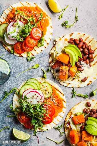 Open vegan tortilla wraps with sweet potato, beans, avocado, tomatoes, pumpkin and seedlings on a gray background, flat lay, top view. Healthy vegan food concept.