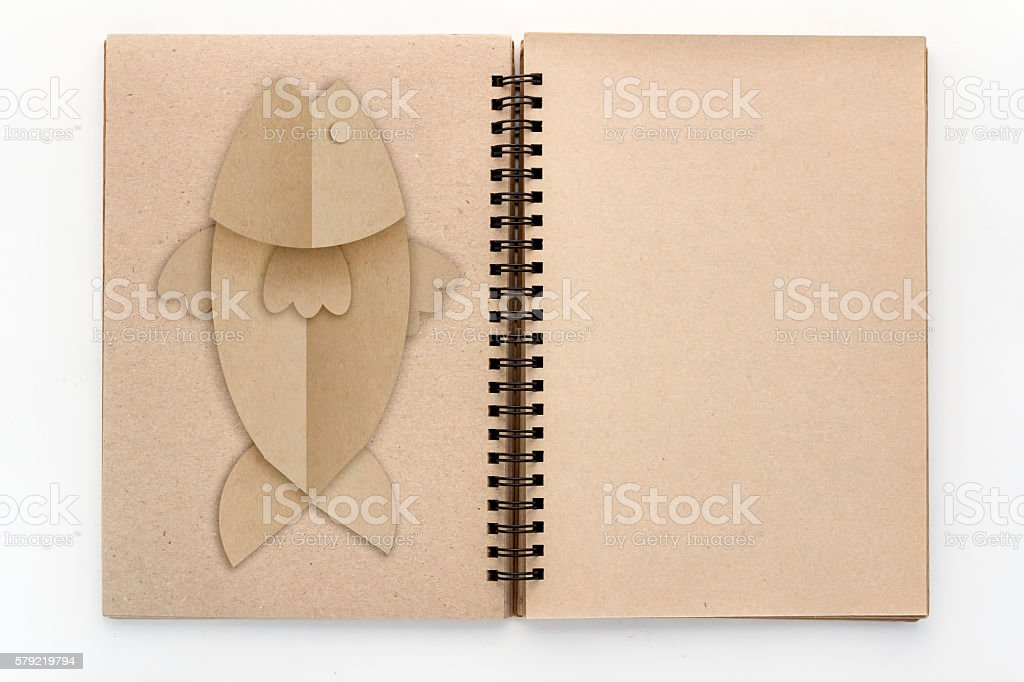 Open Vintage recycle sketch book with fish shape paper cut.jpg stock photo