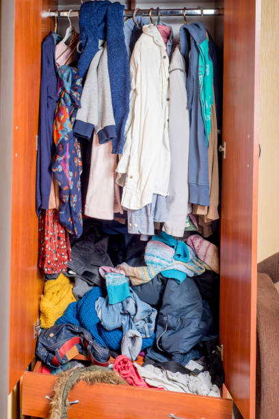 open wardrobe with clothes on hangers and clutter in open drawers stock photo