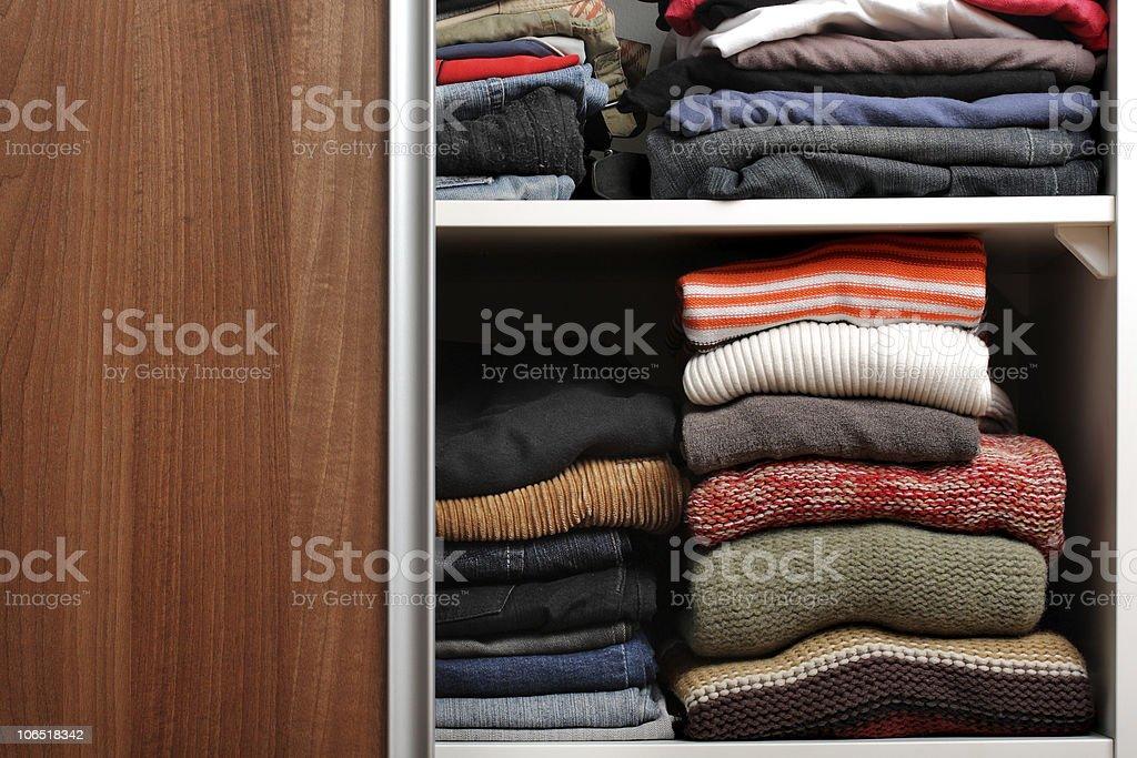 Abrir un armario con un montón de doblado de ropa - foto de stock