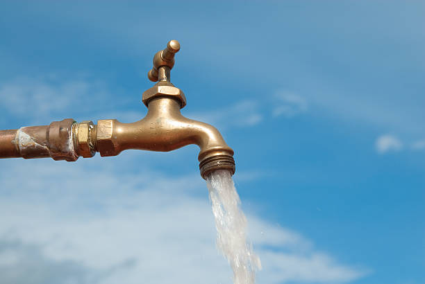 Open water faucet against a blue sky stock photo