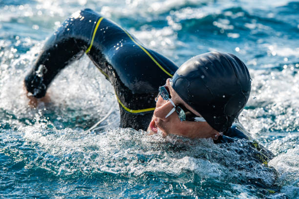 Open water swimmer swimming in sea Male open water swimmer swimming forward crawl in sea. wetsuit stock pictures, royalty-free photos & images
