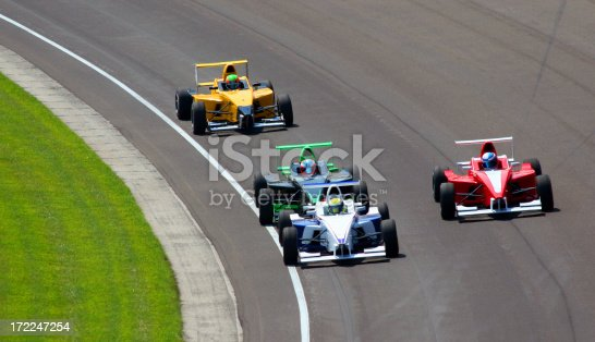 four open wheel cars racing around a turn at the Indianapolis Motor Speedway in Speedway, Indiana